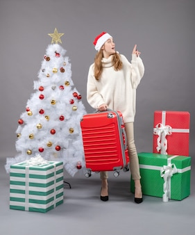 전면보기는 그녀의 빨간 여행 가방을 들고 산타 모자와 함께 크리스마스 소녀를 놀라게