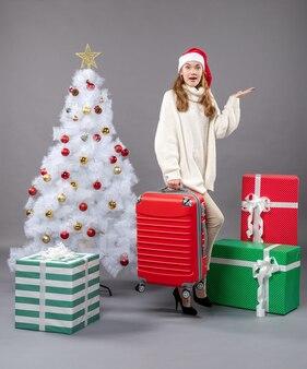 La vista frontale ha sorpreso la ragazza di natale con il cappello della santa che tiene la sua borsa da viaggio vicino all'albero di natale e ai contenitori di regalo