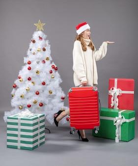 正面図は、クリスマスツリーの近くに彼女の旅行バッグを保持しているサンタの帽子をかぶったクリスマスの女の子を驚かせた