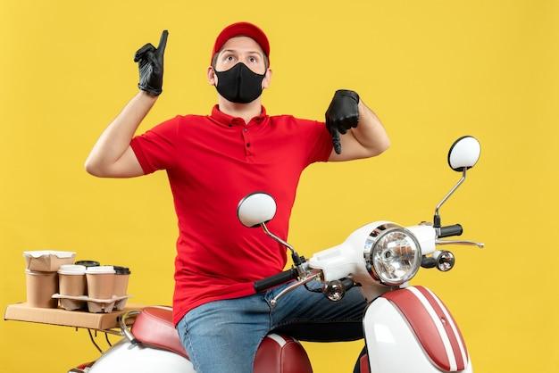 Vista frontale del giovane adulto sorpreso che indossa la camicetta rossa e guanti del cappello nella mascherina medica che trasporta l'ordine che si siede sullo scooter con i pollici su e giù su priorità bassa gialla