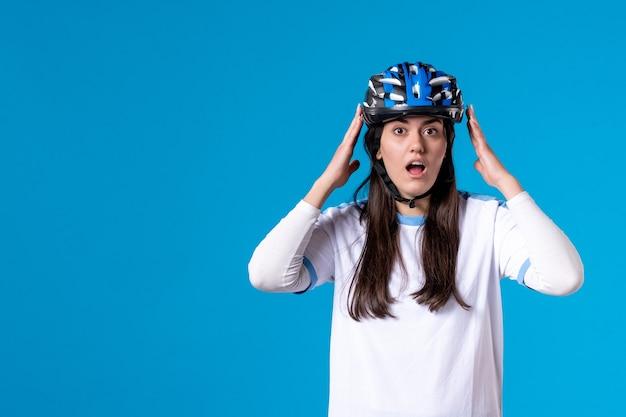 正面図ヘルメットとスポーツ服を着た若い女性を驚かせた