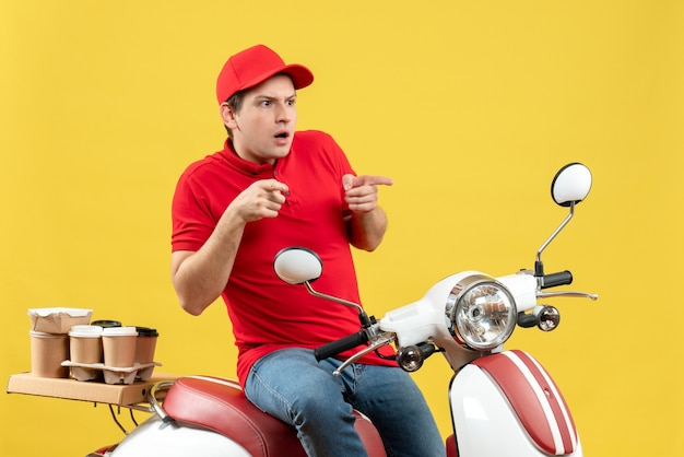 Front view of surprised young guy wearing red blouse and hat delivering orders pointing up on yellow background