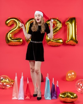 Front view surprised young lady in black dress balloons on red