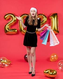 Front view surprised young lady in black dress holding shopping bags balloons on red