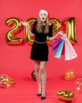 正面図は、赤のショッピング バッグの風船を保持している黒のドレスを着た若い女性を驚かせた