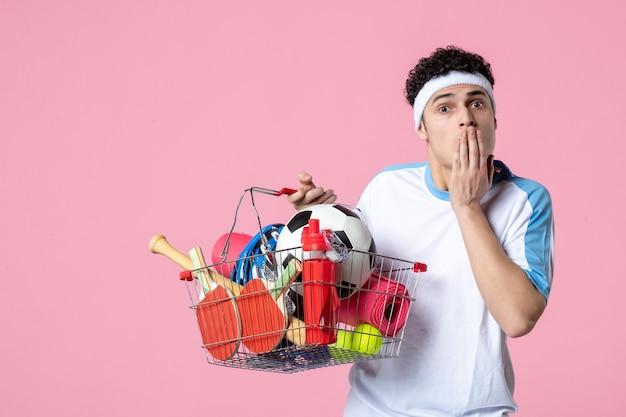 正面図は、スポーツ用品でいっぱいのバスケットとスポーツ服を着た若い男性を驚かせた