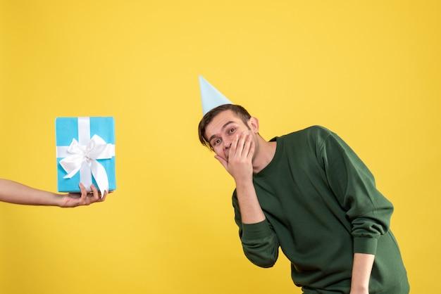 Vista frontale sorpreso giovane uomo regalo in mano umana su giallo