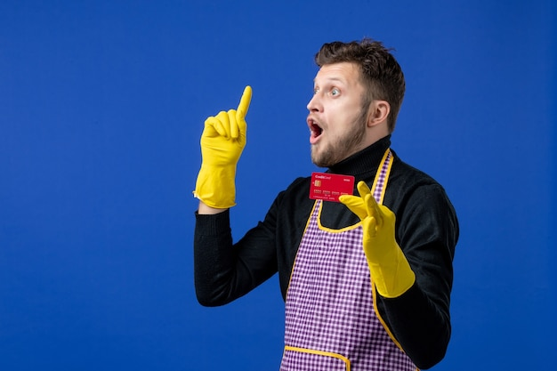 Front view of surprised young man holding card pointing at ceiling on blue wall