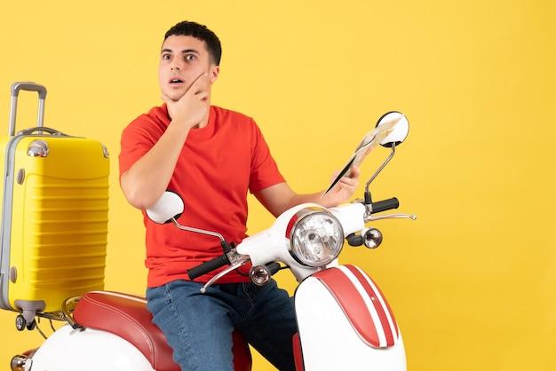 Vista frontale sorpreso giovane uomo sulla mappa della holding del ciclomotore mettendo la mano sul mento