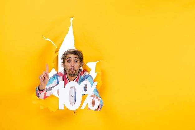 Vista frontale di un giovane sorpreso che mostra il dieci percento e punta verso l'alto in un buco strappato in carta gialla
