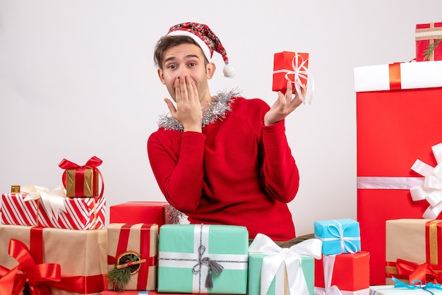 전면보기는 크리스마스 선물 주위에 앉아 젊은 남자를 놀라게