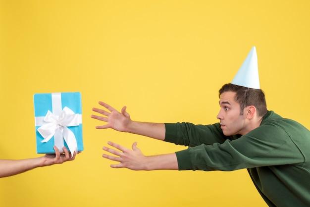 Vista frontale sorpreso giovane uomo che cerca di catturare il regalo in mano umana su giallo