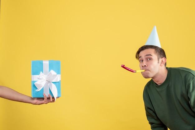 Vista frontale ha sorpreso il giovane che utilizza il regalo del noisemaker in mano umana su colore giallo