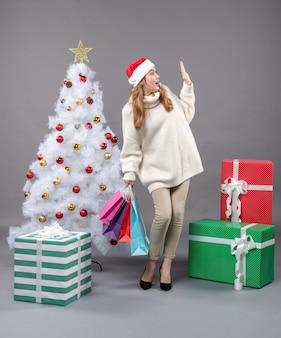 많은 다채로운 쇼핑백을 들고 산타 모자와 함께 전면보기 놀라운 크리스마스 여자