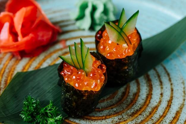 Вид спереди суши гункан с красной икрой и огурцом с васаби и имбирем на тарелке