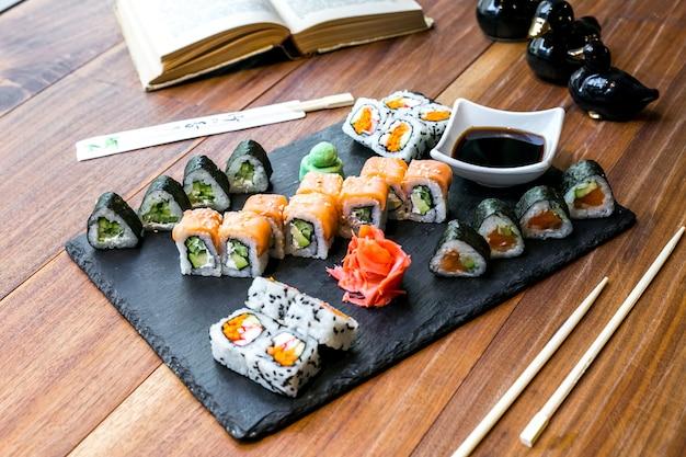 Set di sushi vista frontale rotoli con salsa di soia zenzero e wasabi su un piatto e con un libro sul tavolo