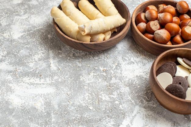Вид спереди сладкие рогалики с печеньем и орехами на белом фоне