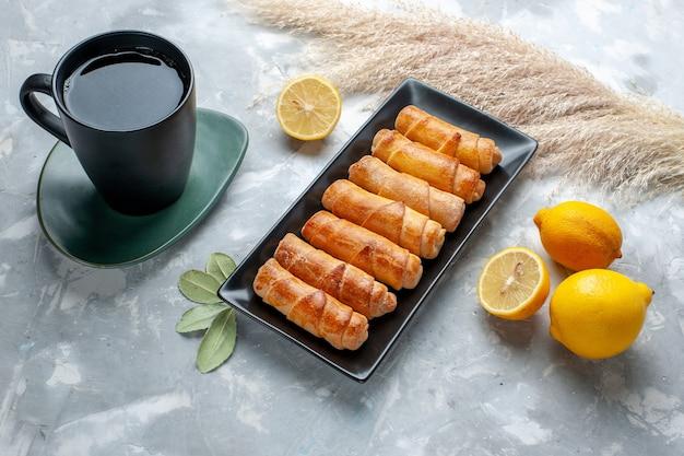 フロントビューレモンとライトテーブルのお茶のカップと甘い腕輪、ペストリーケーキ甘い砂糖を焼く