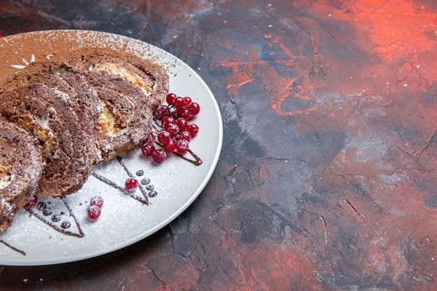 正面図甘いビスケットは暗いテーブルの上にスライスされたクリーミーなケーキをロールバックします