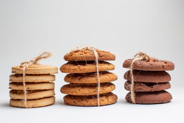 Vista frontale biscotti dolci su biscotti bianchi dessert tè foto torta zucchero cake