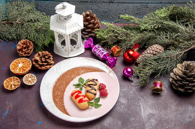 Biscotti dolci vista frontale con albero di natale e giocattoli su spazio buio