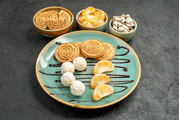Biscotti dolci di vista frontale con le caramelle del cocco sul biscotto grigio del biscotto dello scrittorio dolce