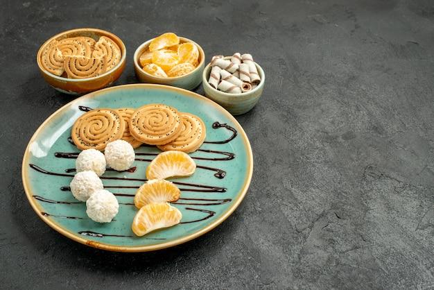 灰色の机の上のココナッツキャンディーと正面図の甘いビスケットビスケットクッキー甘い