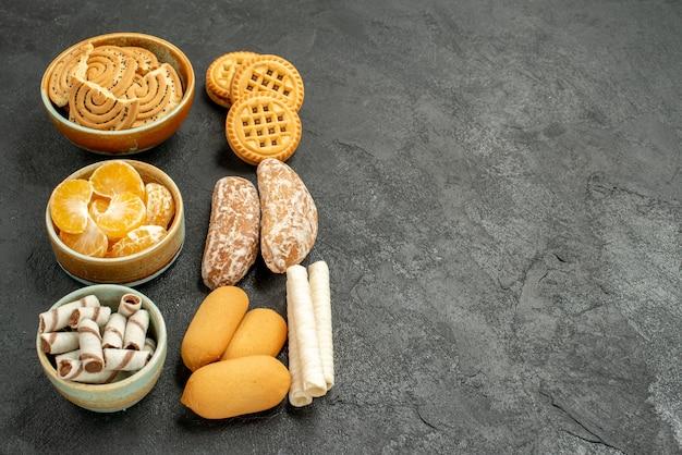 灰色のテーブルにクッキーとフルーツの正面図の甘いビスケット甘いクッキー 無料写真