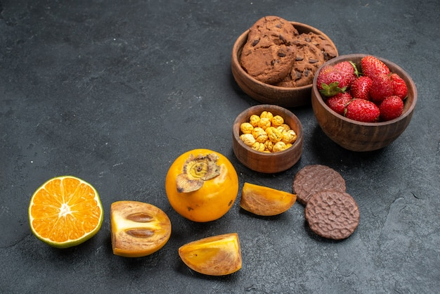 暗い背景に果物と正面の甘いビスケット
