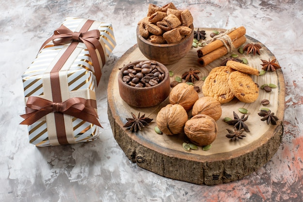 Front view sweet biscuits with presents and walnuts on light background sugar tea color cookie sweet cocoa cake love