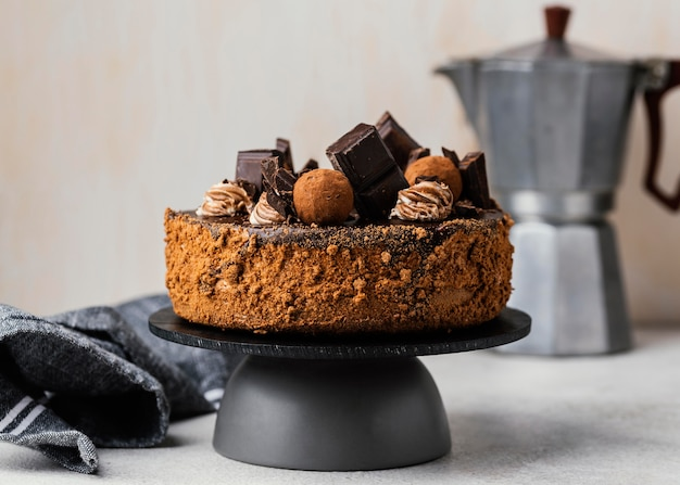 Front view of sweet chocolate cake on stand with kettle