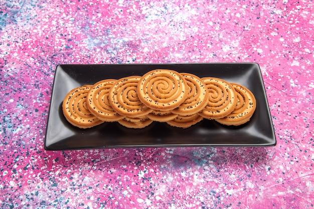 Vista frontale biscotti dolci deliziosi piccoli biscotti all'interno del modulo nero sulla scrivania rosa chiaro.