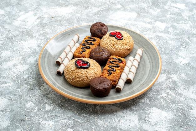 Вид спереди сладкое печенье внутри тарелки на белом пространстве