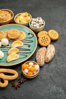 灰色のテーブルにビスケットとキャンディーが付いた正面図の甘いクッキービスケットクッキー甘い
