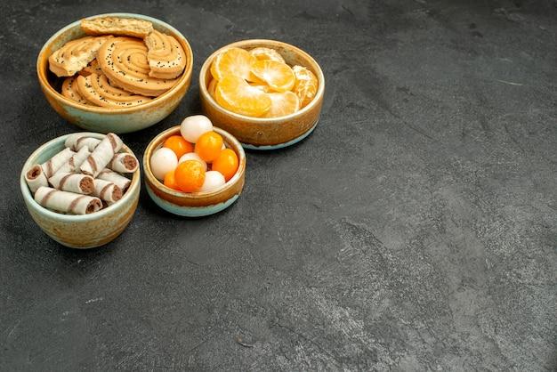 Вид спереди сладкое печенье с конфетами и мандаринами на темном столе, печенье, бисквитное сладкое
