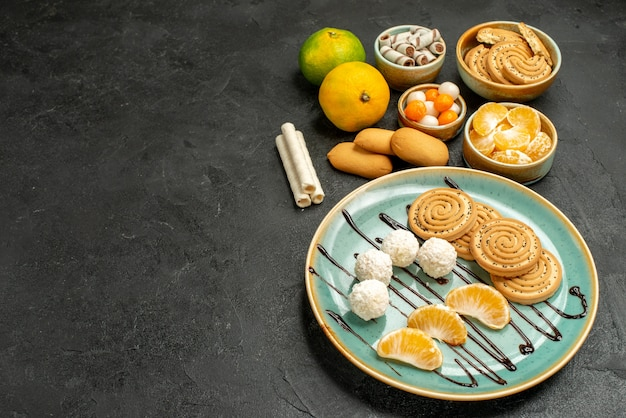 Вид спереди сладкое печенье с конфетами и мандаринами на сером столе, печенье, торт, конфеты