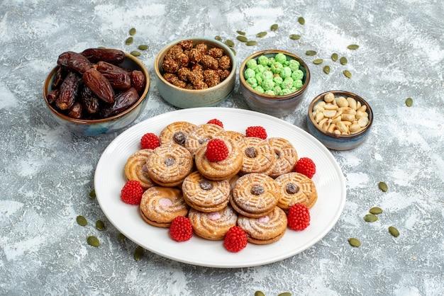 Biscotti dolci di vista frontale con caramelle e confetture su uno spazio bianco