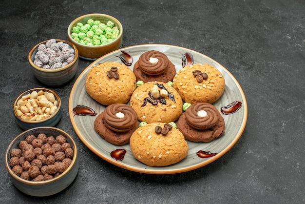 Вид спереди сладкое печенье с конфетами на темно-сером пространстве