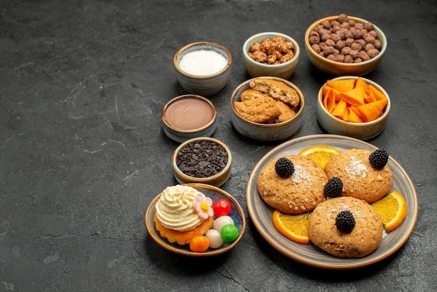 暗い背景にチップとオレンジのスライスが付いた正面図の甘いクッキーフルーティクッキービスケット甘いパイケーキ