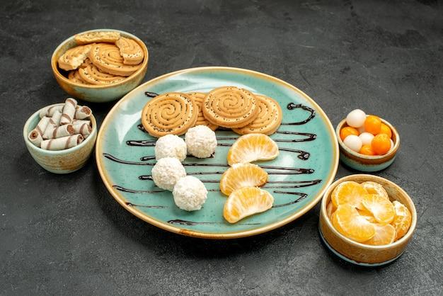 회색 책상 비스킷 케이크 사탕에 코코넛 사탕과 과일 전면보기 달콤한 쿠키