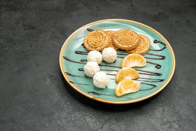 Biscotti dolci di vista frontale con le caramelle del cocco all'interno del piatto sulla torta della caramella del biscotto della scrivania grigio scuro