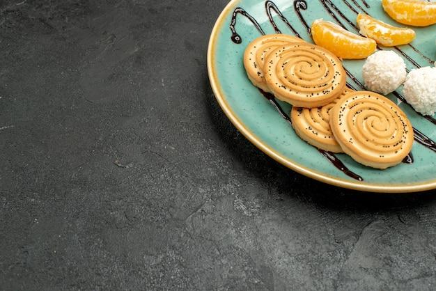 灰色の机の上のプレートの中にココナッツキャンディーが付いている正面図の甘いクッキービスケットキャンディーケーキ