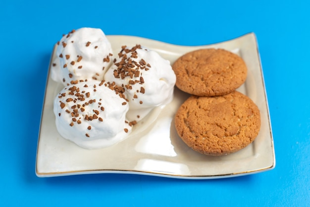 青い机の上のプレートの内側においしいアイスクリームが付いた正面の甘いクッキー
