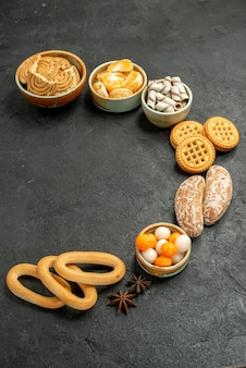 暗いテーブルの上の果物とキャンディーと正面図の甘いクッキークッキービスケット甘い 無料写真