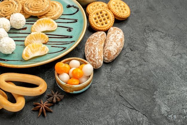 Biscotti dolci di vista frontale con frutta e caramelle sul dolce del biscotto dei biscotti della tavola scura