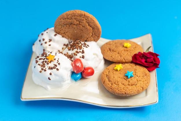 明るいデスクの甘い焼き色のクッキーのプレート内のアイスクリームと正面の甘いクッキー