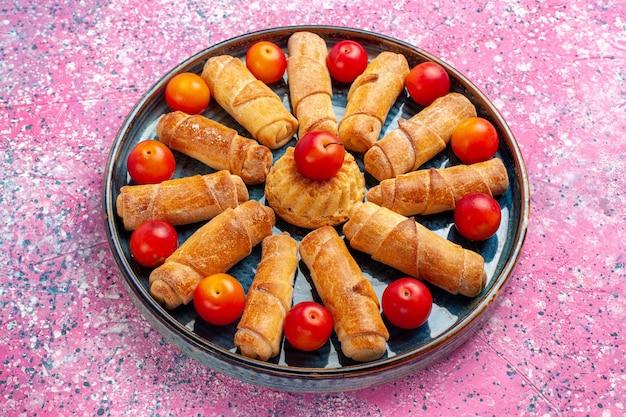 Вид спереди сладкие вкусные рогалики, запеченные пирожные внутри подноса со сливами на розовом столе