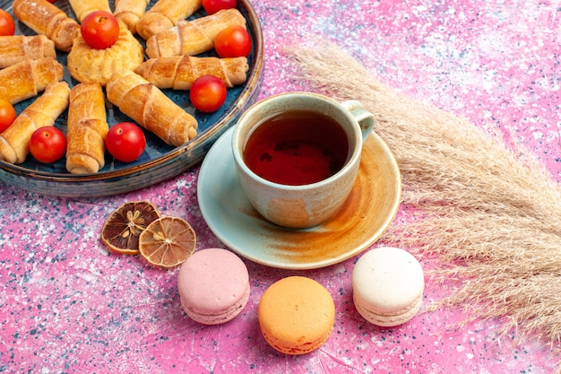Vista frontale dolci deliziosi bagel all'interno del vassoio con macarons francesi di prugne fresche acide e tazza di tè sulla scrivania rosa chiaro