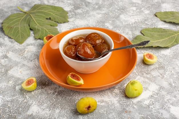 Джем из сладкого инжира, вид спереди, со свежим инжиром внутри оранжевой тарелки на белом столе
