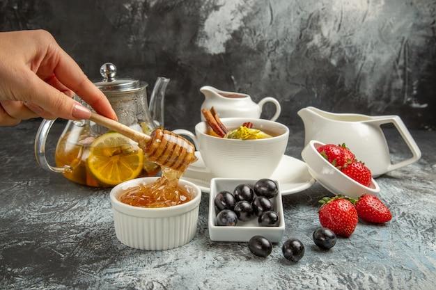 暗い床の朝の食べ物の朝食にお茶とオリーブと甘い蜂蜜の正面図